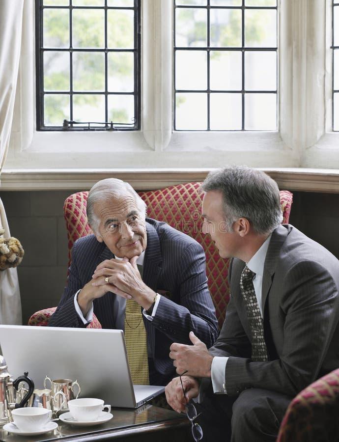 Hombres de negocios que hablan sobre el ordenador portátil en pasillo foto de archivo libre de regalías