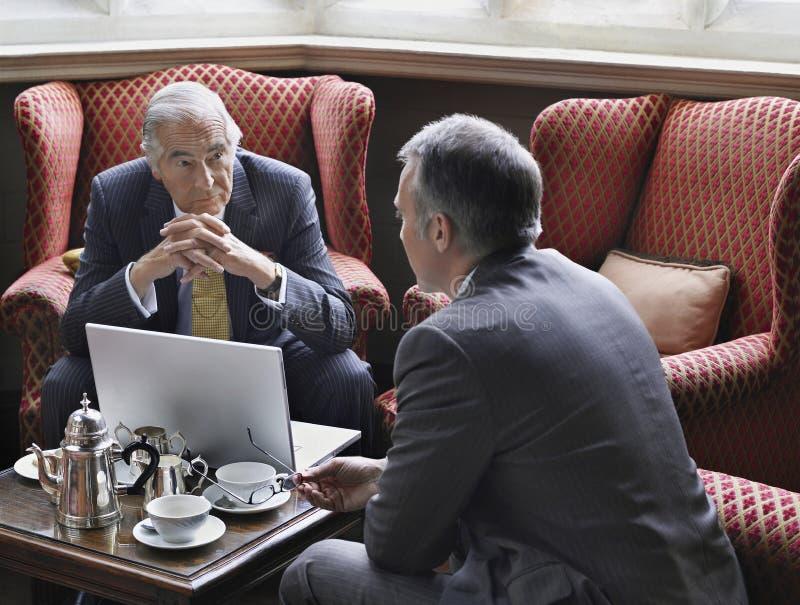 Hombres de negocios que hablan sobre el ordenador portátil en pasillo fotografía de archivo