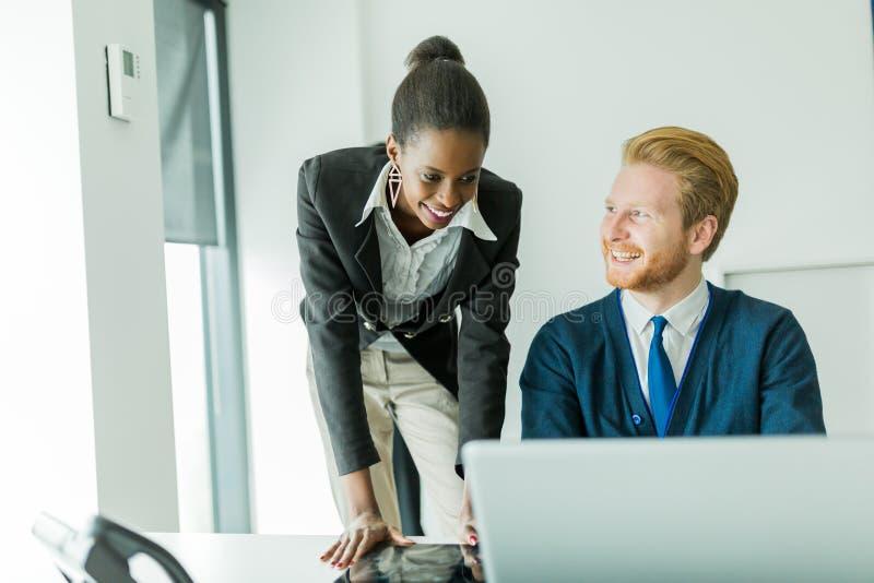 Hombres de negocios que hablan y que sonríen en una oficina delante de un l fotografía de archivo libre de regalías