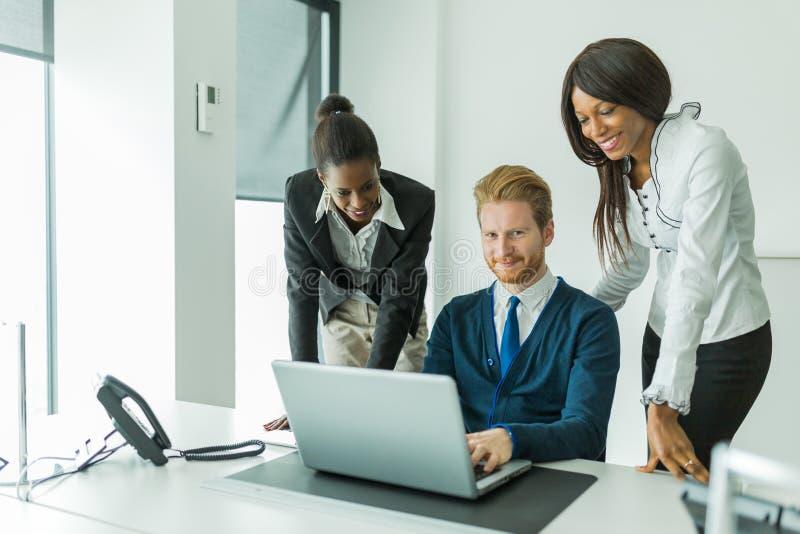 Hombres de negocios que hablan y que sonríen en una oficina delante de un l fotografía de archivo