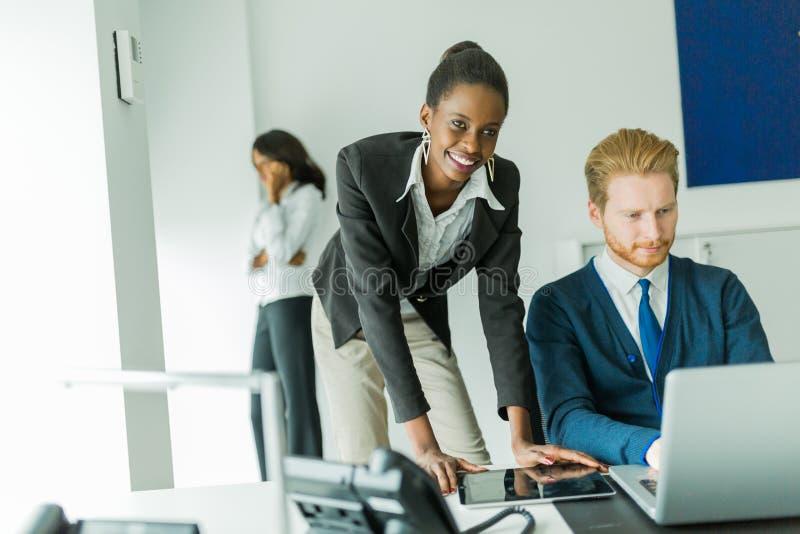 Hombres de negocios que hablan y que sonríen en una oficina delante de un l foto de archivo