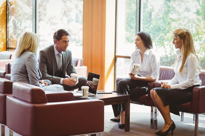 Hombres de negocios que hablan y que trabajan junto en el sofá imágenes de archivo libres de regalías