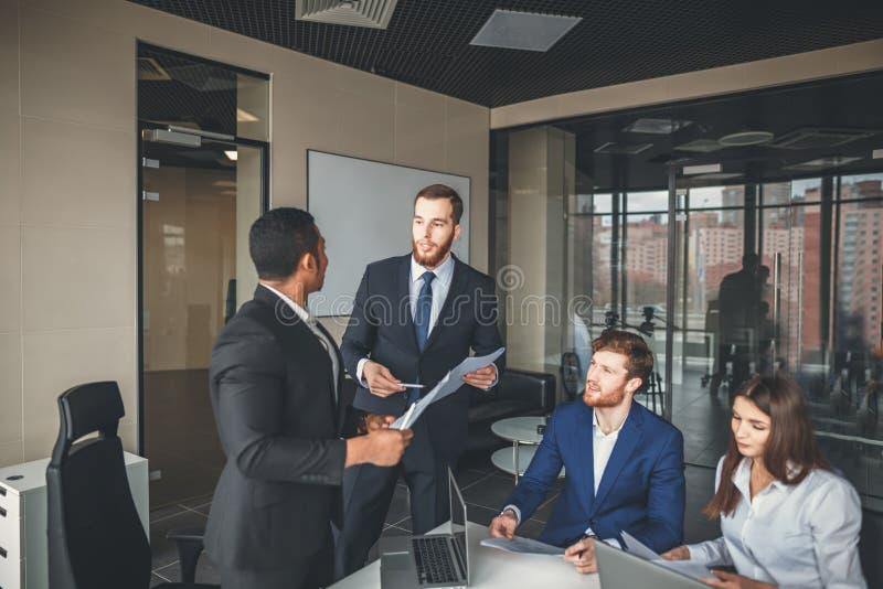 Hombres de negocios que hacen frente a concepto de trabajo de la oficina de la discusión de la comunicación imagenes de archivo