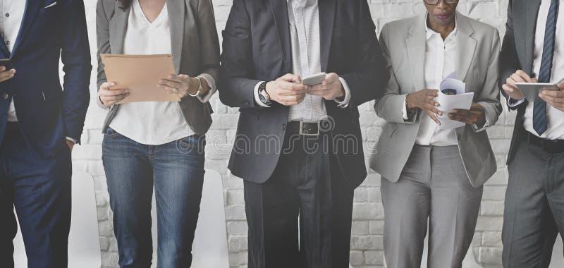 Hombres de negocios que hacen frente a la conexión corporativa del dispositivo de Digitaces concentrada fotografía de archivo libre de regalías