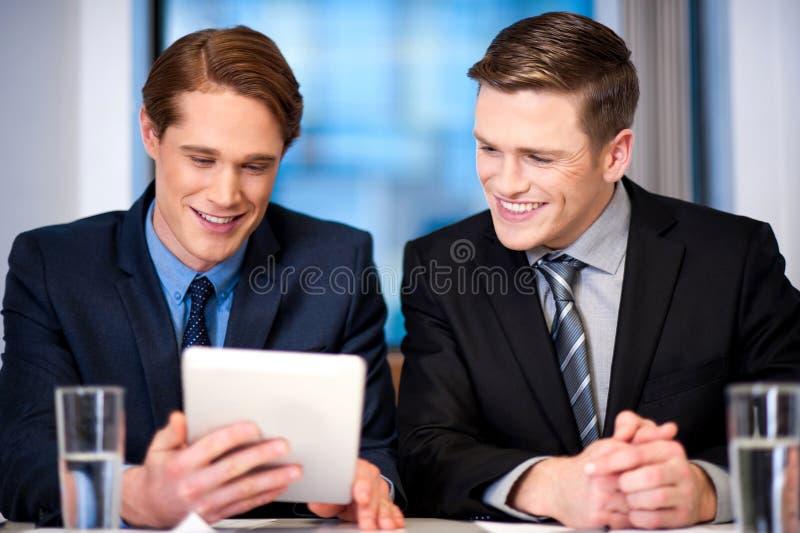 Hombres de negocios que hojean en el dispositivo de la tableta fotos de archivo