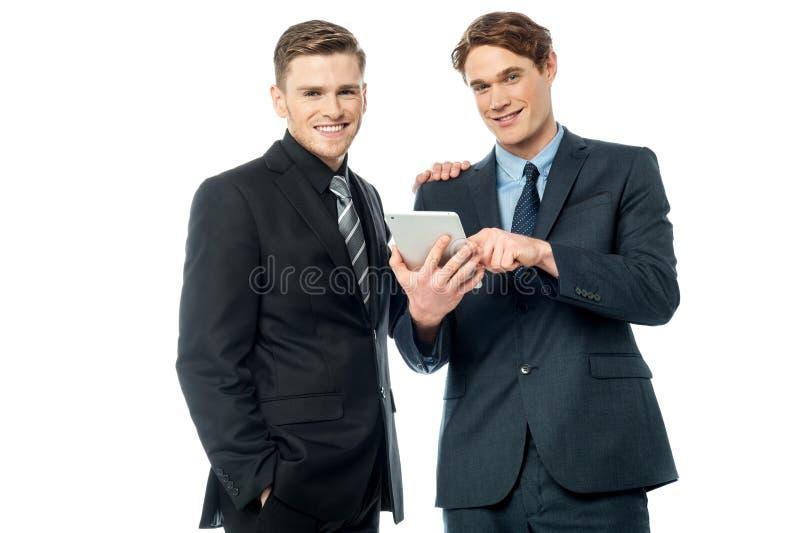 Hombres de negocios que hojean en el dispositivo de la tableta imagenes de archivo