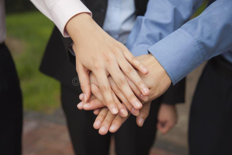 Hombres de negocios que juntan su mano como muestra del funcionamiento del equipo y que la animan, primer fotos de archivo libres de regalías