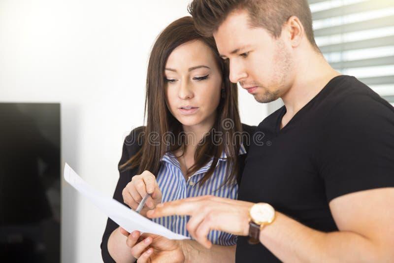 Hombres de negocios que leen el documento en oficina fotos de archivo libres de regalías