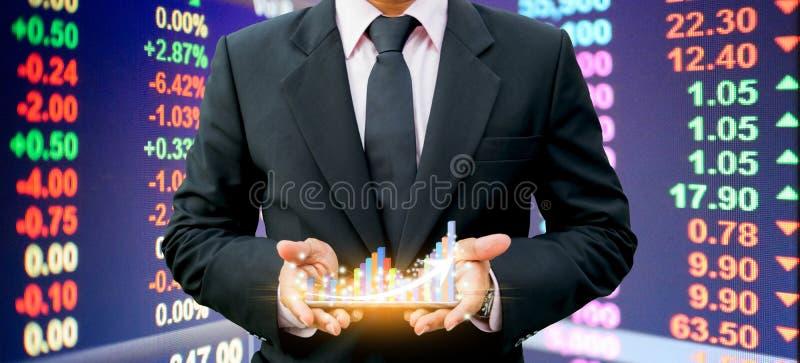 Hombres de negocios que llevan a cabo el gr?fico de barra en la tecnolog?a de la inversi?n del smartphone imagen de archivo