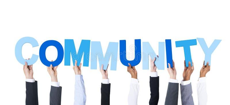 Hombres de negocios que llevan a cabo a la comunidad de la palabra imagen de archivo