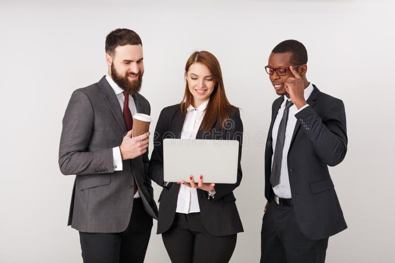 Hombres de negocios que miran el ordenador portátil y la sonrisa foto de archivo