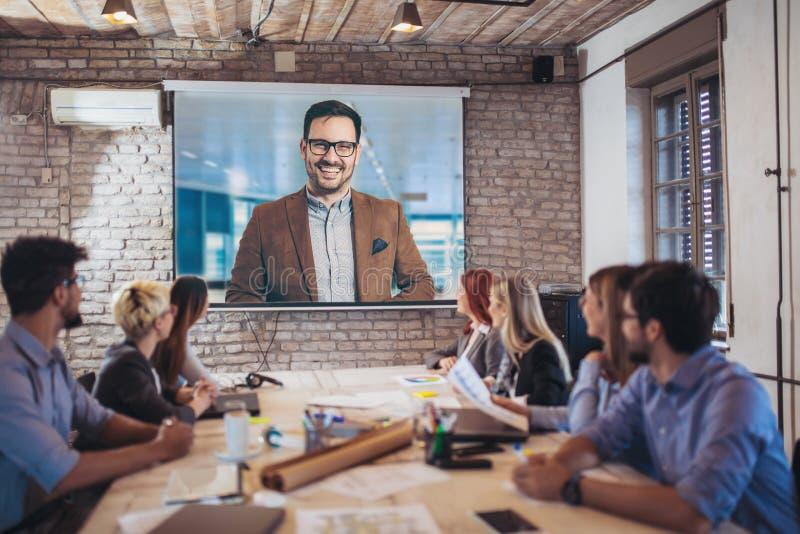 Hombres de negocios que miran el proyector durante videoconferencia fotos de archivo