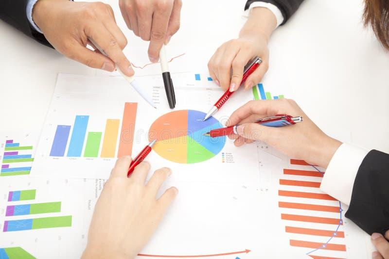 Hombres de negocios que miran informe y que analizan la carta fotografía de archivo
