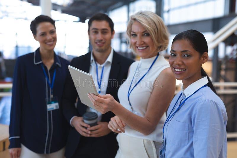 Hombres de negocios que miran la cámara mientras que discute sobre la tableta digital en una oficina moderna fotos de archivo libres de regalías