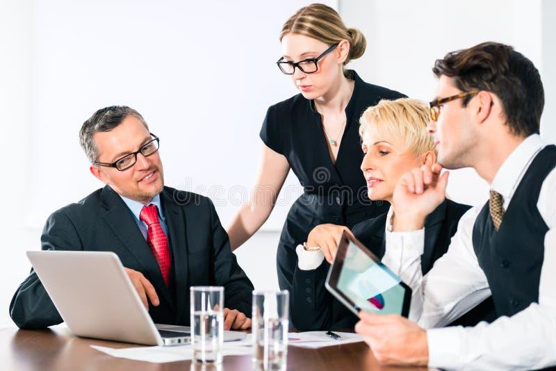 Hombres de negocios que miran la pantalla del ordenador portátil imagen de archivo libre de regalías
