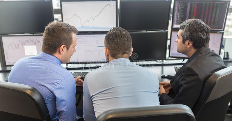 Hombres de negocios que miran las pantallas de ordenador foto de archivo