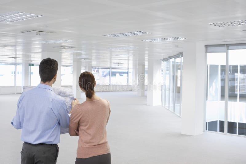 Hombres de negocios que miran plan y el espacio de oficina vacío imágenes de archivo libres de regalías