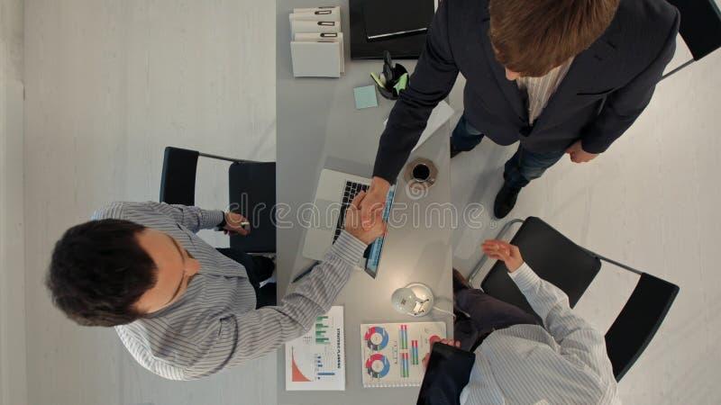 Hombres de negocios que miran su apretón de manos de los colegas Visión superior foto de archivo