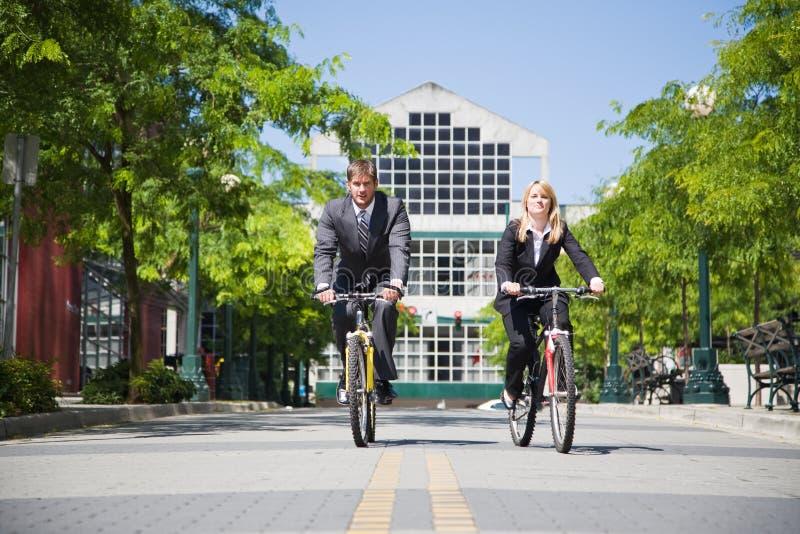 Hombres de negocios que montan la bicicleta imagenes de archivo