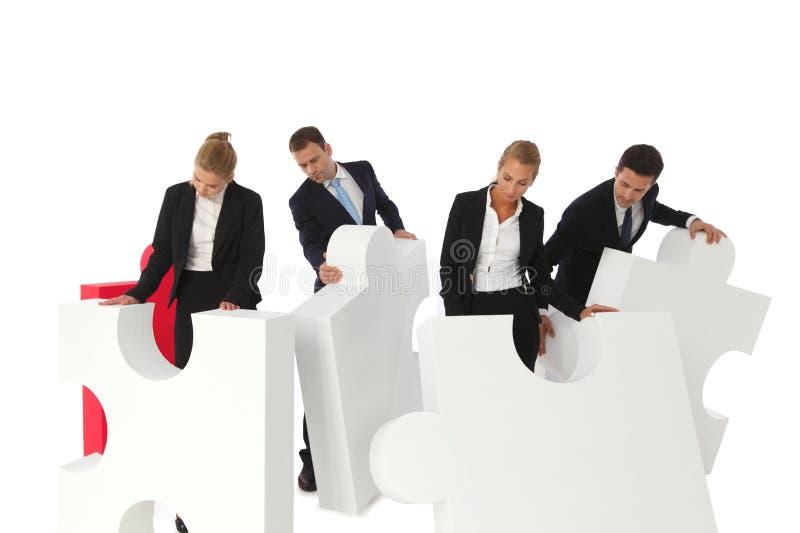 Hombres de negocios que montan rompecabezas imagenes de archivo