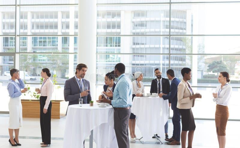 Hombres de negocios que obran recíprocamente con uno a en la tabla durante un seminario imagen de archivo