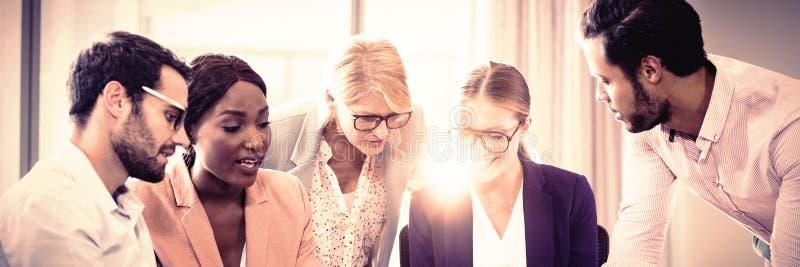 Hombres de negocios que obran recíprocamente usando el ordenador portátil, el teléfono móvil y la tableta digital foto de archivo libre de regalías