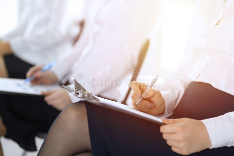 Hombres de negocios que participan en la conferencia o que entrenan en la oficina, primer Mujeres que se sientan en sillas y que  imagen de archivo libre de regalías