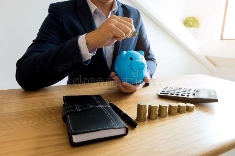 Hombres de negocios que ponen la moneda en la hucha azul, dinero de ahorro finan fotos de archivo libres de regalías