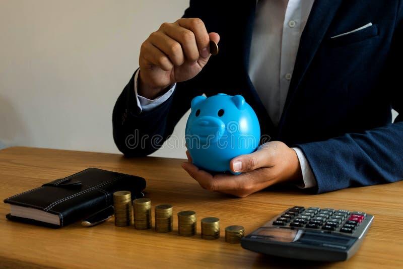 Hombres de negocios que ponen la moneda en la hucha azul, dinero de ahorro finan foto de archivo
