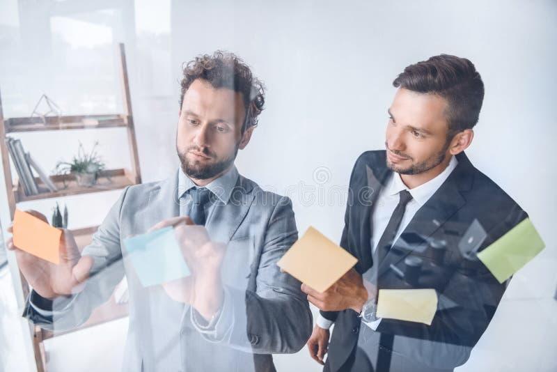Hombres de negocios que ponen notas pegajosas en el vidrio mientras que trabaja en oficina fotografía de archivo libre de regalías