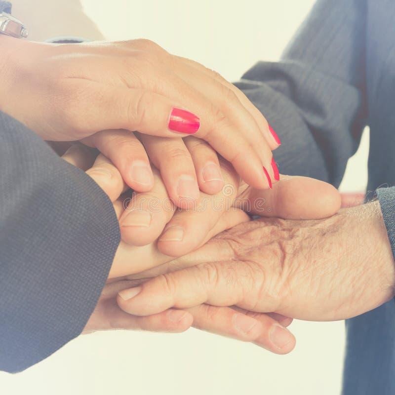 Hombres de negocios que ponen sus manos juntas Arma la consolidación fotografía de archivo