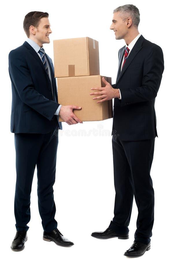 Hombres de negocios que presentan con las cajas de cartón fotos de archivo