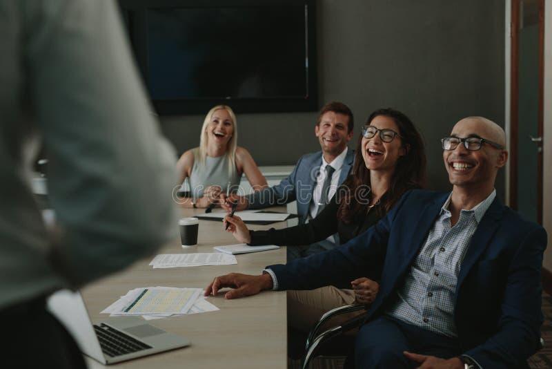 Hombres de negocios que ríen durante una reunión de la conferencia fotos de archivo