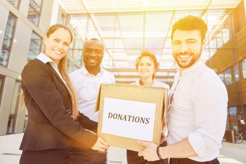 Hombres de negocios que recogen donaciones delante de la oficina imagenes de archivo