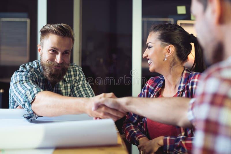 Hombres de negocios que sacuden las manos, acabando para arriba una reunión foto de archivo