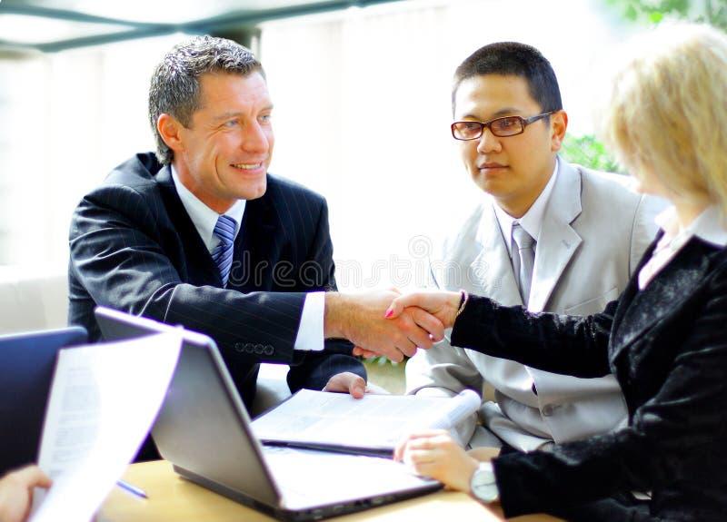 Hombres de negocios que sacuden las manos, acabando para arriba una reunión imagen de archivo libre de regalías