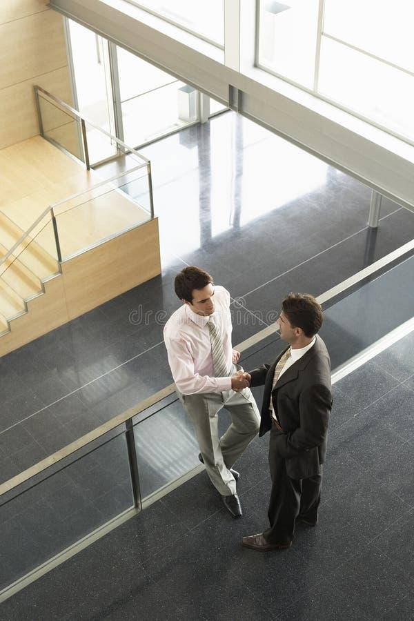 Hombres de negocios que sacuden las manos cercando con barandilla en oficina fotografía de archivo libre de regalías