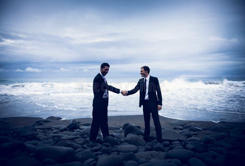 Hombres de negocios que sacuden las manos con el fondo tempestuoso del océano imagen de archivo