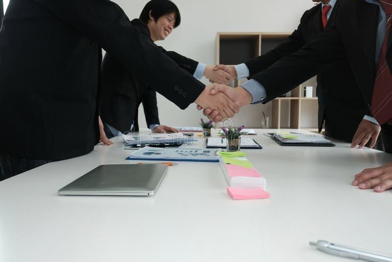 Hombres de negocios que sacuden las manos después de acabar para arriba que se encuentra Dos co fotografía de archivo