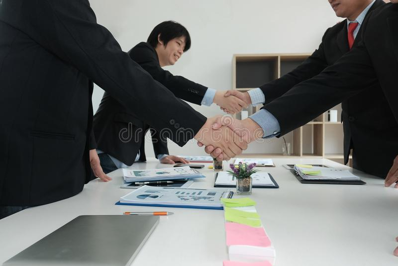 Hombres de negocios que sacuden las manos después de acabar para arriba que se encuentra Dos co fotos de archivo libres de regalías