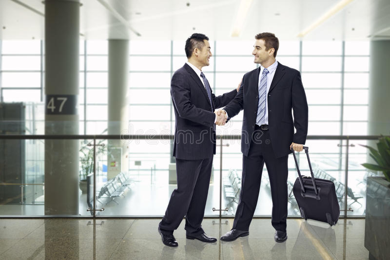 Hombres de negocios que sacuden las manos en el aeropuerto imagen de archivo libre de regalías