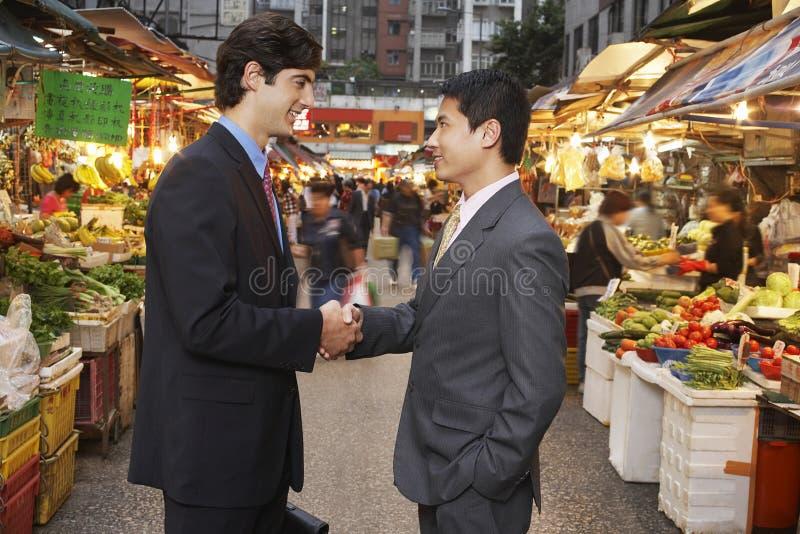 Hombres de negocios que sacuden las manos en el mercado callejero fotos de archivo libres de regalías