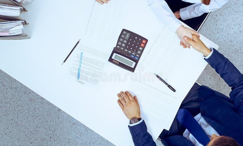 Hombres de negocios que sacuden las manos en la reuni?n, visi?n desde arriba Contable o inspector financiero que hace el informe, imagenes de archivo