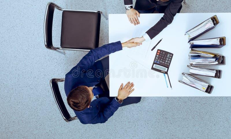 Hombres de negocios que sacuden las manos en la reuni?n, visi?n desde arriba Contable o inspector financiero que hace el informe, imagen de archivo
