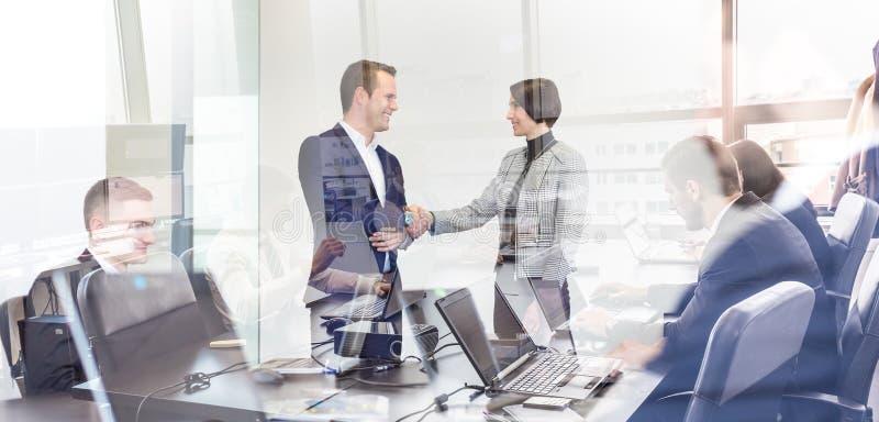 Hombres de negocios que sacuden las manos en oficina corporativa del moder fotos de archivo