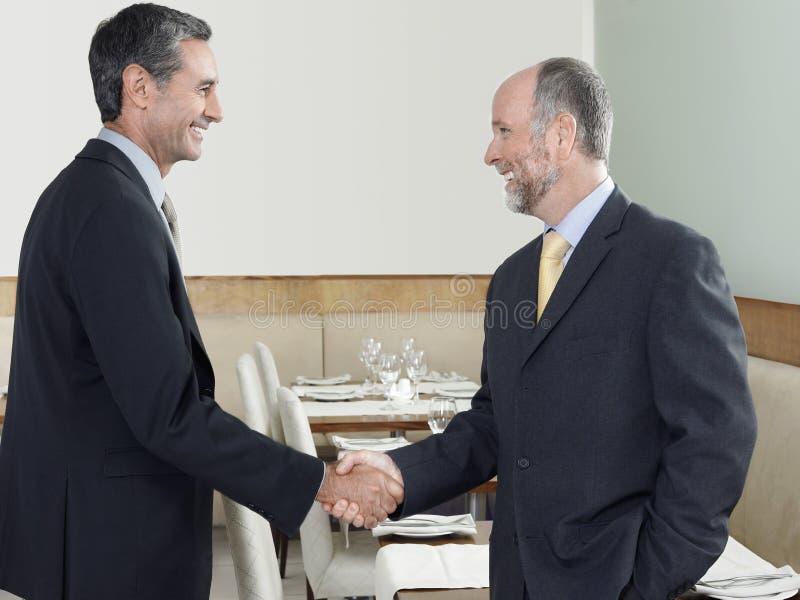 Hombres de negocios que sacuden las manos en restaurante imagenes de archivo