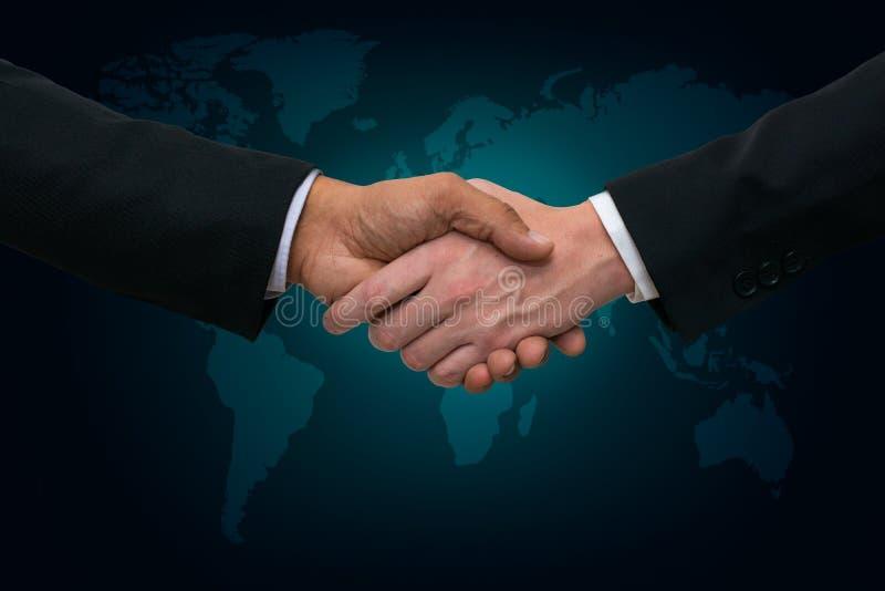 Hombres de negocios que sacuden las manos en un mapa del mundo con el fondo del verde azul foto de archivo