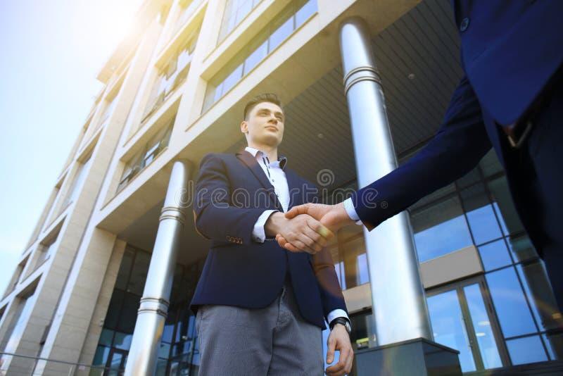 Hombres de negocios que sacuden las manos fuera del edificio de oficinas moderno fotografía de archivo libre de regalías