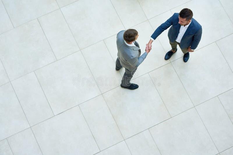 Hombres de negocios que sacuden las manos, visión superior fotografía de archivo libre de regalías