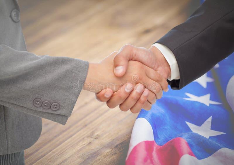 Hombres de negocios que sacuden sus manos contra bandera americana imagenes de archivo